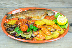 Trout with vegetables on a clay plate Stock Photography