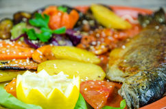 Trout with vegetables on a clay plate Royalty Free Stock Photo