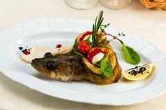 Trout with vegetables under parmesan sauce stock images