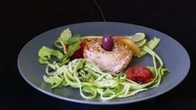 Trout with white wine sauce and zucchini pasta. 360 rotation on black stock video