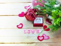 Trouwring op giftvakje met harten en bloemen op houten lijst, de dagachtergrond van Valentine ` s Stock Foto
