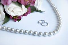 Trouwringen, bloemen, parels op een witte backgroun Royalty-vrije Stock Afbeelding