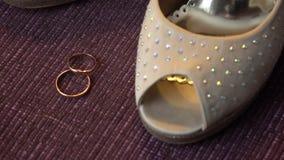 Trouwringen dichtbij de schoenen van de bruid stock videobeelden