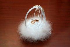 Trouwringen die in een witte pluizige mand leggen royalty-vrije stock afbeelding