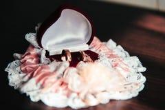 Trouwringen in een vakje en een kouseband van de bruid op de houten lijst stock afbeelding