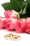 Trouwringen en rozen stock afbeeldingen