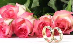 Trouwringen en rozen stock fotografie