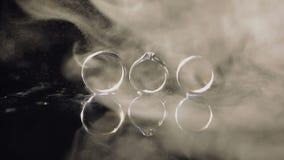 Trouwringen en verlovingsring die op donkere waterspiegel liggen die met licht glanzen Sluit omhoog macro Ringen in waterpaar stock videobeelden