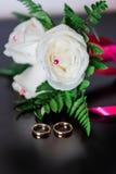 Trouwringen en witte rozen stock fotografie