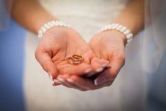 Trouwringen in handen van de bruid het meisje biedt te huwen aan Vrolijk me Trouwringen in de palmen van de bruid royalty-vrije stock foto