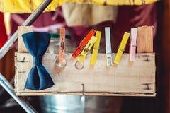Trouwringen met betrekking tot een houten doos met gekleurde wasknijpers Royalty-vrije Stock Afbeeldingen