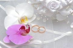 Trouwringen met orchideebloemen en bruidssluier op grijs Royalty-vrije Stock Foto's