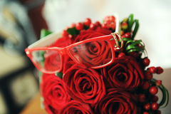 Trouwringen op de glazen en een rood boeket Stock Afbeelding