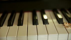 Trouwringen op de sleutels van de oude piano stock footage