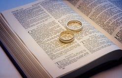 Trouwringen op een Bijbel Stock Foto