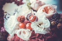 Trouwringen op een boeket van kleurrijke bloemen Stock Fotografie