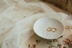 Trouwringen op een ceramische witte schotel naast een stoffensluier royalty-vrije stock foto