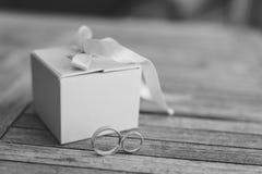 Trouwringen op een lichte houten textuur in een blauwe doos Huwelijk j Stock Afbeelding