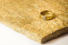 Trouwringen op een natuursteen met opneming van inheems goud Aanbiedingshanden en harten Stock Afbeeldingen
