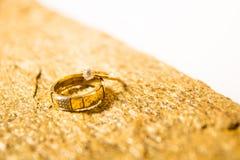 Trouwringen op een natuursteen met opneming van inheems goud Aanbiedingshanden en harten Royalty-vrije Stock Foto