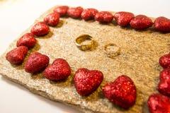 Trouwringen op een natuursteen met opneming van inheems goud Aanbiedingshanden en harten Stock Foto's