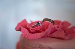 Trouwringen op een roze cake royalty-vrije stock afbeeldingen