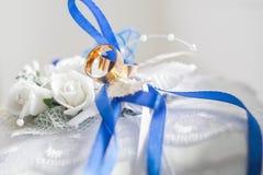 Trouwringen op een zacht hoofdkussen met blauwe lintclose-up Stock Afbeelding