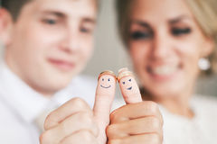 Trouwringen op hun die vingers met de bruid en de bruidegom worden geschilderd stock afbeelding