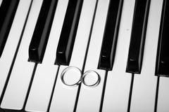 Trouwringen op piano stock foto