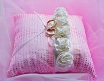 Trouwringen op roze kussen Stock Fotografie