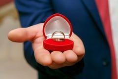 Trouwringen in rode doos in de hand van de bruidegom Royalty-vrije Stock Afbeelding
