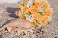 Trouwringen in shell op het strand Stock Afbeeldingen