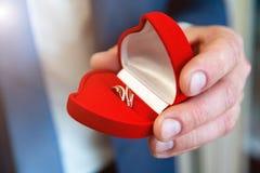 Trouwringen ter beschikking Trouwringen in de handen van de bruidegom stock foto