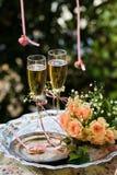 Trouwringen vóór de ceremonie, met verfraaide Champagne-glazen en rozen Stock Afbeelding