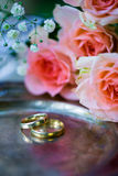 Trouwringen vóór de ceremonie, met verfraaide Champagne-glazen en rozen Stock Foto