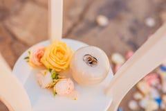 Trouwringen van een onlangs-gehuwd paar op een kussen voor ringen Stock Afbeeldingen