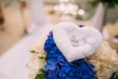 Trouwringen van een onlangs-gehuwd paar op een kussen voor ringen Stock Foto's