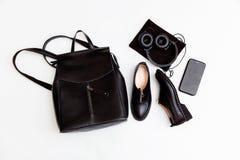 A trouxa, as sapatas, o telefone e os fones de ouvido das mulheres no preto Acess?rios de forma de couro das mulheres Configura?? imagem de stock