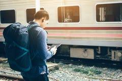 Trouxa asiática do homem para o curso no estação de caminhos-de-ferro e na tabuleta da utilização Fotos de Stock Royalty Free