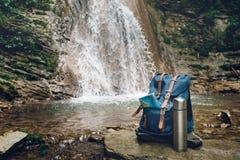 Trouxa, mapa e garrafa térmica azuis do moderno Vista do fundo da cachoeira de Front Tourist Traveler Bag On Caminhada da aventur foto de stock royalty free