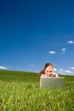 Trovandosi nell'erba con il Internet Fotografia Stock Libera da Diritti