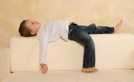 Trovandosi su un sofà Fotografia Stock