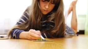 Trovandosi sul pavimento sullo stomaco, la ragazza disegna con un pennarello nero archivi video
