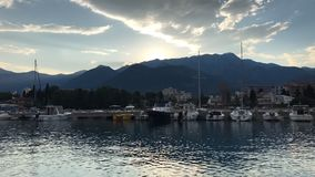 Trow de la salida del sol del claro del verano que las montañas en puerto deportivo con muchos barcos navegan en timelapse almacen de video