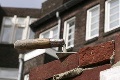 Trowel on brick wall Stock Image