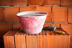 Trowel, bucket and bricks Stock Images