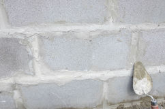 Trowel on cinderblock gray background. against the background of the brickwork is trowel. Stock Photography