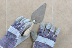 Trowel and construction gloves. On the floor. top view Royalty Free Stock Photo