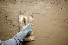 Trowel with glove hand plastering cement mortar. Dirty trowel with glove hand plastering cement mortar in the wall Royalty Free Stock Photo