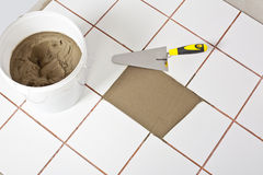 Trowel and old white tiles with tile adhesive Stock Photos